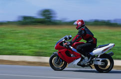 Motorcyclist. Biker riding on a road Stock Images