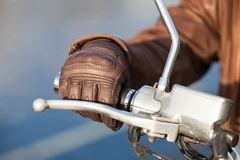 Motorcyclist arm in brown leather glove holds twist grip throttle, close up view Royalty Free Stock Images