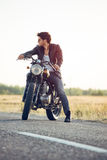 Motorcyclist with a cafe-racer motorcycle outdoors. Motorcyclist with a cafe-racer motorcycle royalty free stock photo