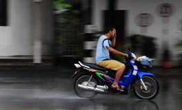 Motorcyclist covers his eyes driving through a mon. No helmet motorcyclist covers his eyes while driving in a monsoon rainstorm Stock Images