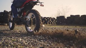 Motorcyclist doing tire burnout in the desert, slow motion. Professional motorcyclist drift and turns on a motorcycle on the groun. D, a biker does a trick on a stock footage