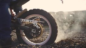 Motorcyclist doing tire burnout in the desert, slow motion. Professional motorcyclist drift and turns on a motorcycle on the groun. D, a biker does a trick on a stock video footage