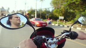Motorcyclist drives motorcycle on asphalt road while traveling in tropical island during beautiful sunset in slow motion stock footage