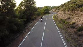Motorcyclist driving his motorbike on the mountain road in the country side. Aerial view. stock video footage