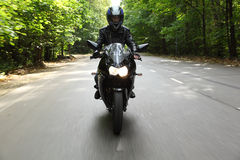 Motorcyclist goes on road, front view Royalty Free Stock Photo