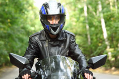 Motorcyclist goes on road, front view, closeup stock photography
