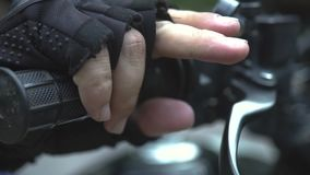 Motorcyclist hands pushing breaks on handlebar close up. Male hands in moto gloves holding breaks on steering wheel. Motorcyclist hands pushing breaks on stock footage