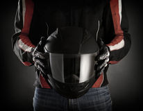 Motorcyclist with helmet in his hands.  Dark background Royalty Free Stock Photos