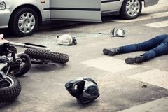 Motorcyclist helmet and motorbike on the street after collision. With a car concept photo royalty free stock photography