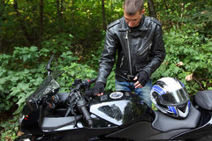 Motorcyclist and his bike in forest Stock Images