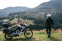 Motorcyclist look to distance with his touristic motorcycle, with big bags ready for a long trip, black style, white helmet, ride stock image