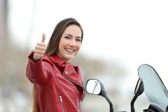 Motorcyclist looking at camera with thumb up outdoors Stock Photos