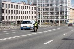 Motorcyclist and minibus on the road against the backdrop of modern buildings. St. Petersburg, Russia - May 04, 2019: motorcyclist and minibus ride on an asphalt stock images
