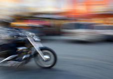 Motorcyclist in motion going down the street Royalty Free Stock Images