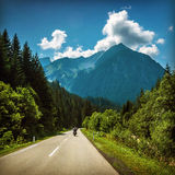 Motorcyclist on mountainous highway. Motorcyclist riding on mountainous highway, Euro tour on motorbike, road pass along Alps mountains, extreme sport, freedom royalty free stock photos