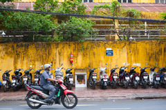 Motorcyclist moves by motorcycle parking lot, Saigon. HO CHI MINH, VIETNAM - JULY 5, 2014: An unidentified motorcyclist moves by a parking lot full of Royalty Free Stock Photo
