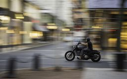 A motorcyclist moving at speed with a blur effect on the background and on the vehicle. A motorcyclist moving at speed with a blur effect on the background and stock image