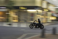 A motorcyclist moving at speed with a blur effect on the background and on the vehicle. A motorcyclist moving at speed with a blur effect on the background and stock photos