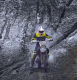Motorcyclist overcomes the obstacle of mud Stock Photography