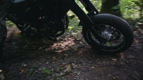Motorcyclist in protective gear and boots, performing drift around its axis on Enduro. Steadicam shot of a motorcyclist in protective gear and boots performing a stock footage