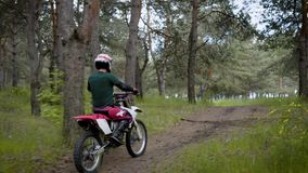 A motorcyclist in a protective helmet at a uniform is riding along a country road through a forest on a vehicle stock video