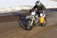 Motorcyclist racing in the winter track. Royalty Free Stock Images