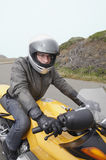 Motorcyclist ready to ride. Man on a yellow motorcycle Stock Photos