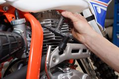 Motorcyclist replaces, checks the glow plug in a motorcycle stock photo