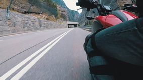 Motorcyclist Rides along on the Scenic Mountain Curve Road. Side view. POV. Motorcyclist Rides along on the Scenic Mountain Curve Road. Side view of a stock video footage