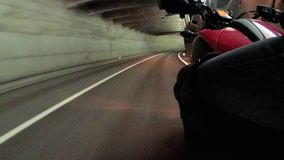 Motorcyclist Rides along on the Scenic Mountain Curve Road in Tunnel. Side view. POV. Motorcyclist Rides along on the Scenic Mountain Curve Road in Tunnel. Side stock footage