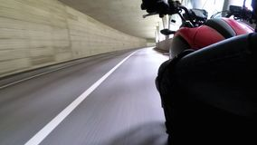 Motorcyclist Rides along on the Scenic Mountain Curve Road in Tunnel. Side view. POV. Motorcyclist Rides along on the Scenic Mountain Curve Road in Tunnel. Side stock video footage