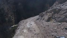 A motorcyclist rides on a dangerous mountain road
