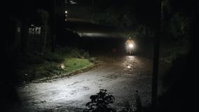 Motorcyclist rides on a wet road late at night in the rain. View on rain and lamp. stock video