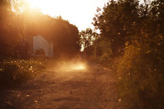 Motorcyclist riding along dusty road Stock Photography