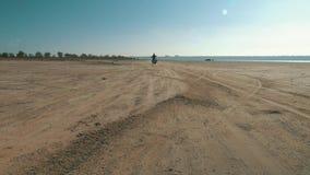 Motorcyclist riding along sandy beach. Biker rides motorcycle through desert. Motorcyclist riding along the sandy beach. Biker rides a motorcycle through the stock footage