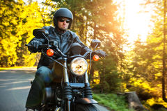 Motorcyclist riding chopper on a road. Motorcyclist riding a chopper on a road in morning sun stock images