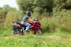 Motorcyclist riding on country road stock image