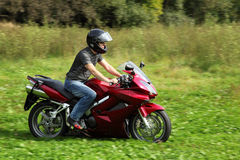 Motorcyclist riding on meadow. Summer royalty free stock photography