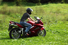 Motorcyclist riding on meadow Royalty Free Stock Photo
