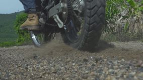 Motorcyclist riding on motorcycle on gravel countryside road. Moto biker driving on motorcycle in off road. Moto sport. And travel. Motorcycle lifestyle stock footage
