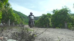 Motorcyclist riding on rear wheel on gravel countryside road. Motorcycle rider driving on rear wheel on off road. Moto. Sport and travel. Motorcycle lifestyle stock video