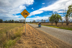 Motorcyclist on the road with tractors crossing sign Stock Images