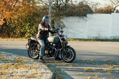 Motorcyclist sits on an old cafe-racer motorcycle, autumn background Stock Photography