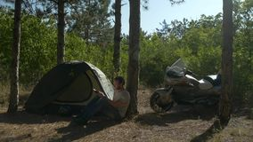 Motorcyclist sitting near tent in woods and reading a book at vacation near camp stock video