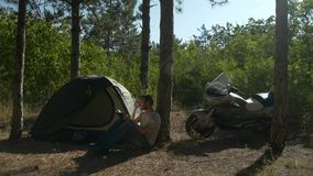 Motorcyclist sitting near tent in woods and writing a book at vacation near camp stock video footage