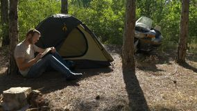 Motorcyclist sitting near tent in woods and writing a book at vacation near camp stock video