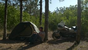 Motorcyclist sitting near tree in woods and playing stick at vacation near camp stock video