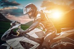 Motorcyclist on sport bike stands on the edge of the mountains in the background of a bright sunset. Motorcyclist in helmet on motorcycle against mountains and Stock Photography