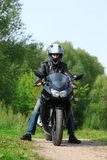 Motorcyclist standing on country road Royalty Free Stock Images