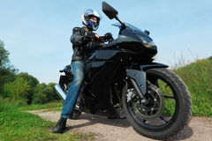 Motorcyclist standing on country road, bottom view stock photos